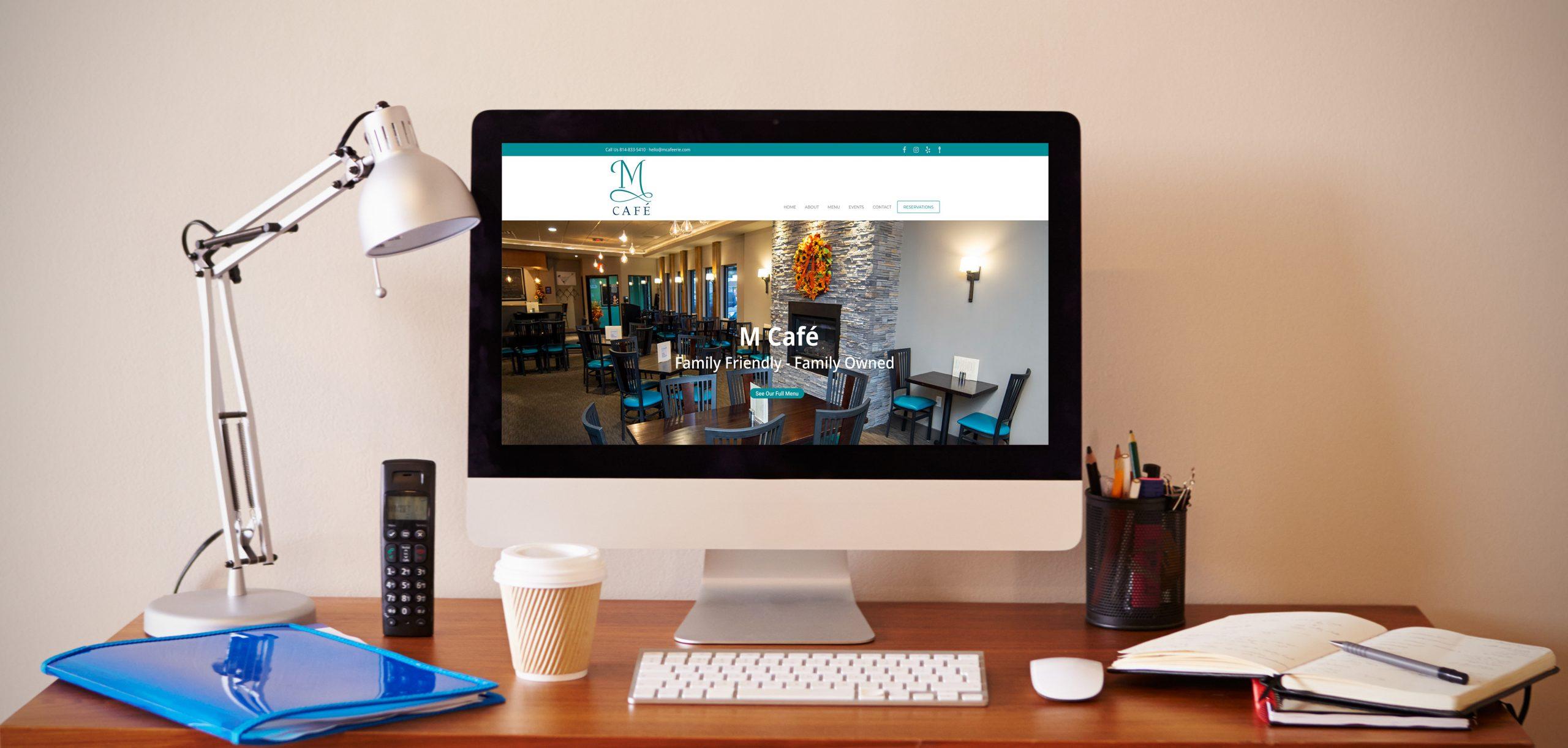 Computer on a desk showing M Cafe website